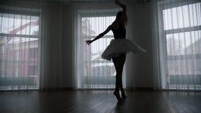 Ένα στούντιο στο λυκόφως Μια σκιαγραφία του νέου ballerina γυναικών που εκτελεί μια περιστροφή απόθεμα βίντεο