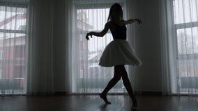 Ένα στούντιο στο λυκόφως Μια σκιαγραφία του νέου ballerina γυναικών που εκπαιδεύει την που περιστρέφει μπροστά από το παράθυρο φιλμ μικρού μήκους