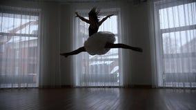 Ένα στούντιο στο λυκόφως Μια σκιαγραφία του νέου ballerina γυναικών δημιουργεί και πηδά την εκτέλεση μιας διάσπασης στον αέρα απόθεμα βίντεο
