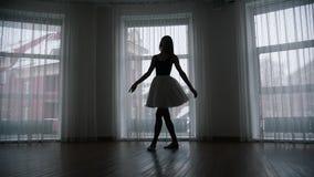Ένα στούντιο στο λυκόφως Μια σκιαγραφία του νέου ballerina γυναικών στο tutu που εκπαιδεύει την που περιστρέφει μπροστά από το πα απόθεμα βίντεο