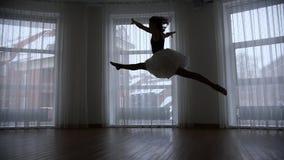 Ένα στούντιο στο λυκόφως Μια σκιαγραφία του ballerina δημιουργεί και πηδά την εκτέλεση μιας διάσπασης στον αέρα απόθεμα βίντεο