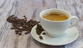 Ένα φλυτζάνι του ευώδους μαύρου καφέ και μια χούφτα των φασολιών καφέ σε μια παλαιά ξύλινη επιτραπέζια κινηματογράφηση σε πρώτο π στοκ φωτογραφίες με δικαίωμα ελεύθερης χρήσης