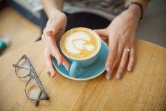 Ένα φλυτζάνι του cappuccino στα χέρια ενός κοριτσιού Πρωί με τον καφέ το σπίτι καφέ cappuccino μπάρμαν προετοιμάζεται στοκ εικόνα