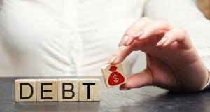 Ένα χέρι βάζει έναν ξύλινο φραγμό με μια εικόνα δολαρίων και το χρέος λέξης Πληρωμή των φόρων και του χρέους στο κράτος Έννοια οι στοκ φωτογραφία με δικαίωμα ελεύθερης χρήσης