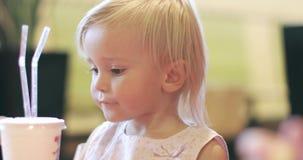Ένα χαριτωμένο μικρό κορίτσι τρώει τα τηγανητάπατατών Â και πίνει ένα κοκτέιλ απόθεμα βίντεο