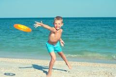 Ένα παιδί παίζει με ένα frisbee στην παραλία στοκ εικόνα