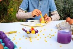 Ένα παιδί που χρωματίζει τα αυγά Πάσχας Δραστηριότητα παιδιών Πάσχας στοκ φωτογραφίες