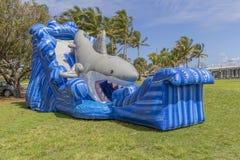 Ένα πλήρως διογκωμένο μεγάλο σπίτι αναπήδησης καρχαριών με τις τεράστιες στάσεις κυμάτων ψηλές στο πάρκο στοκ φωτογραφία