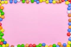 Ένα πλαίσιο των ζωηρόχρωμων σοκολατών Άποψη κινηματογραφήσεων σε πρώτο πλάνο του τοπ, ρόδινου υποβάθρου στοκ εικόνες