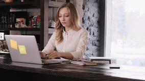 Ένα πορτρέτο ενός ελκυστικού ξανθού κοριτσιού σε ένα άσπρο πουκάμισο κατά τρόπο μεθοδικό παίρνει αποφασιστικά να λειτουργήσει και απόθεμα βίντεο