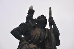 Ένα πουλί που στηρίζεται σε ένα σκοτεινό άγαλμα στοκ εικόνες με δικαίωμα ελεύθερης χρήσης