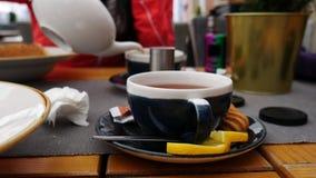 Έννοια ανθρώπων και ποτών - το χέρι μιας γυναίκας χύνει το τσάι σε ένα φλυτζάνι σε έναν καφέ απόθεμα βίντεο