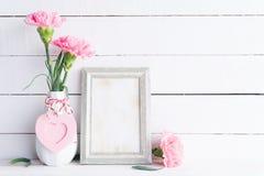 Έννοια ημέρας και αγάπης βαλεντίνων Ρόδινο λουλούδι γαρίφαλων στο βάζο με το παλαιό εκλεκτής ποιότητας πλαίσιο εικόνων και την κό στοκ φωτογραφίες
