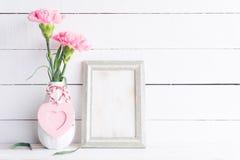 Έννοια ημέρας και αγάπης βαλεντίνων Ρόδινο λουλούδι γαρίφαλων στο βάζο με το παλαιό εκλεκτής ποιότητας πλαίσιο εικόνων και την κό στοκ φωτογραφία με δικαίωμα ελεύθερης χρήσης