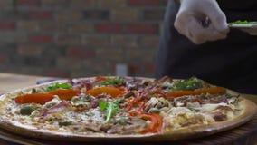 Έννοια διακοσμήσεων τροφίμων Μάγειρας αρχιμαγείρων που διακοσμεί τη μαγειρευμένη πίτσα με τα φρέσκα χορτάρια στα ιταλικά pizzeria φιλμ μικρού μήκους