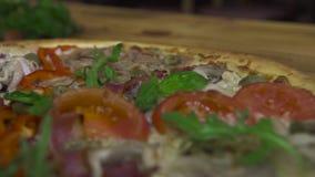 έννοια σχεδίου τροφίμων Μάγειρας αρχιμαγείρων που διακοσμεί τη μαγειρευμένη πίτσα με τα φρέσκα χορτάρια στα ιταλικά pizzeria Ιταλ φιλμ μικρού μήκους
