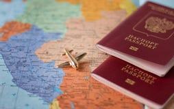 Έννοια ταξιδιού και τουρισμού με τα ταξιδιωτικά έγγραφα διαβατηρίων, αεροπλάνο στο υπόβαθρο παγκόσμιων χαρτών στοκ εικόνα