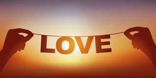 Έννοια της αγάπης με τα χέρια που κρατούν ένα έμβλημα στο οποίο γράφεται την αγάπη λέξης στοκ φωτογραφία