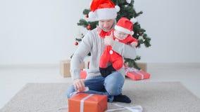 Έννοια Χριστουγέννων Το χαριτωμένο μωρό του μπαμπά παραδίδει το καπέλο Άγιου Βασίλη φιλμ μικρού μήκους