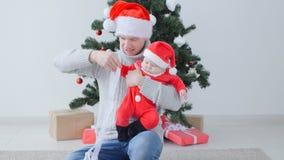 Έννοια Χριστουγέννων Το χαριτωμένο μωρό του μπαμπά παραδίδει το καπέλο Άγιου Βασίλη απόθεμα βίντεο