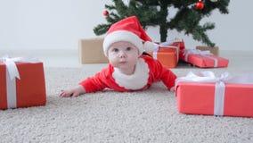 Έννοια Χριστουγέννων Χαριτωμένο μωρό στο κοστούμι Άγιου Βασίλη, που φαίνεται ένα δώρο απόθεμα βίντεο