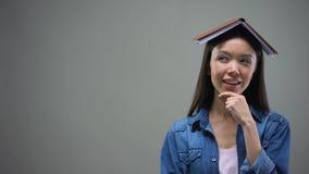 Έξυπνη γυναίκα με το βιβλίο στο κεφάλι που σκέφτεται πέρα από τις ιδέες για το νέο ξεκίνημα, υπολογισμοί φιλμ μικρού μήκους