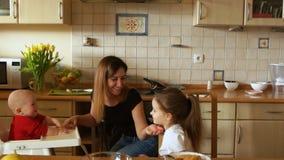 Έξυπνη μητέρα με δύο παιδιά στην κουζίνα Μια γυναίκα ταΐζει δύο παιδιά το λουλούδι ημέρας δίνει το γιο μητέρων mum απόθεμα βίντεο