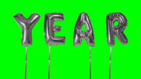 Έτος λέξης από τις ασημένιες επιστολές μπαλονιών ηλίου που επιπλέουν στην πράσινη οθόνη - απόθεμα βίντεο