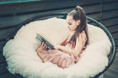 Έφηβος κοριτσιών σε ένα ρόδινο φόρεμα που διαβάζει ένα βιβλίο στοκ εικόνα με δικαίωμα ελεύθερης χρήσης