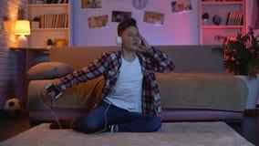 Έφηβος στα ακουστικά που ακούει τη μουσική που προσποιείται να παίξει την ηλεκτρική κιθάρα απόθεμα βίντεο