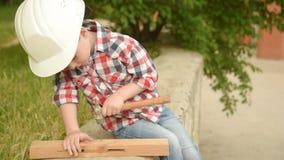 Αγοράκι σε ένα κράνος οικοδόμησης scoopes ένα καρφί φιλμ μικρού μήκους