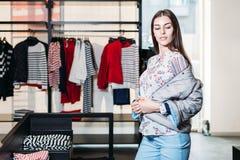 Αγορές, μόδα, ύφος, πώληση, αγορές, επιχείρηση και άνθρωποι όμορφη ευτυχής νέα γυναίκα έννοιας στο κατάστημα ιματισμού Επιχείρηση στοκ εικόνα