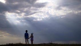 Αγόρι με το περπάτημα κοριτσιών σε ένα υπόβαθρο των όμορφων σύννεφων στο βράδυ στοκ φωτογραφία