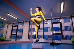 Αθλητική νέα γυναίκα που χρησιμοποιεί την πλατφόρμα βημάτων στη γυμναστική στοκ εικόνες με δικαίωμα ελεύθερης χρήσης