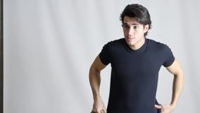 Αθλητικό άτομο που αφαιρεί το πουλόβερ στη μαύρη μπλούζα απόθεμα βίντεο