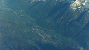 Αιχμές βουνών, απόμακρος αερολιμένας και αλπικές πόλεις σε μια κοιλάδα στοκ φωτογραφίες