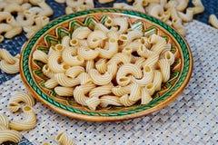 ακατέργαστα whole-grain ζυμαρικά σε ένα πιάτο σε ένα ψάθινο ύφασμα στον πίνακα Τοπ όψη στοκ εικόνες με δικαίωμα ελεύθερης χρήσης