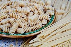 ακατέργαστα whole-grain ζυμαρικά σε ένα πιάτο σε ένα ψάθινο ύφασμα στον πίνακα Τοπ όψη στοκ εικόνα