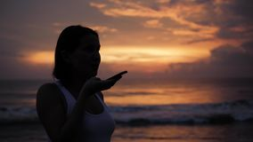 Ακουστική αναγνώριση φωνής AI μηνυμάτων στη με ελεύθερα χέρια ομιλία smartphone Νέα όμορφη ευτυχής γυναίκα σκιαγραφιών ηλιοβασιλέ απόθεμα βίντεο
