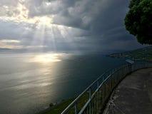 Ακτίνα να διαπερνήσει ηλιοφάνειας μέσω των βαριών σύννεφων στη λίμνη Léman στοκ εικόνα