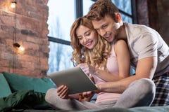 Ακτινοβολώντας συνεδρίαση ζευγών στο comfy κρεβάτι τους και χρησιμοποίηση της ταμπλέτας στοκ εικόνες