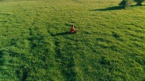 Ακτινωτή πτήση χαμηλού υψομέτρου πέρα από το άτομο αθλητικής γιόγκας στην τέλεια πράσινη χλόη Ηλιοβασίλεμα στο βουνό φιλμ μικρού μήκους