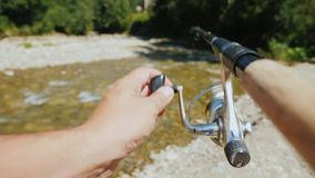 Αλιεύοντας σε έναν μικρό ποταμό βουνών, στο πλαίσιο του χεριού ενός ψαρά με μια ράβδο αλιείας φιλμ μικρού μήκους
