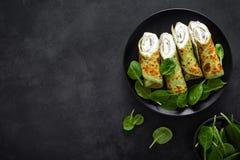 Αλμυρός crepes με το σπανάκι και το τυρί φέτας στο μαύρο υπόβαθρο, τοπ άποψη στοκ εικόνες