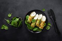 Αλμυρός crepes με το σπανάκι και το τυρί φέτας στο μαύρο υπόβαθρο, τοπ άποψη στοκ εικόνες με δικαίωμα ελεύθερης χρήσης