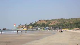 Αμμώδης παραλία ενάντια στη θάλασσα και τα χρωματισμένα σπίτια σε έναν λόφο, άνθρωποι που περπατούν κατά μήκος της παραλίας και π απόθεμα βίντεο