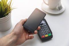 Ανέπαφες πληρωμές Nfc - τηλέφωνο εκμετάλλευσης χεριών επάνω από το τερματικό πληρωμής στοκ φωτογραφίες με δικαίωμα ελεύθερης χρήσης