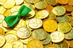 ανασκόπηση ημέρα Πάτρικ s ST Χρυσά νομίσματα με το τριφύλλι, πράσινος δεσμός τόξων, σύμβολα ημέρας του ST Πάτρικ στοκ φωτογραφία με δικαίωμα ελεύθερης χρήσης