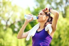 Αναψυχή της νέας φίλαθλης γυναίκας με με το βραχίονα αυξημένος στο επικεφαλής και πόσιμο νερό στη φύση, πάρκο, δασικό υπόβαθρο στοκ εικόνες