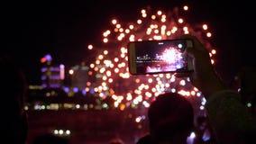 Ανθρώπινη μαγνητοσκόπηση smartphone εκμετάλλευσης χεριών ένα βίντεο των πυροτεχνημάτων, των ανθρώπων και των κτηρίων νύχτας στο υ απόθεμα βίντεο
